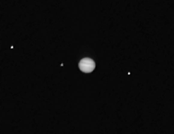 This composite image showing Jupiter (center) and three of its moons -- Callisto (left), Io, and Ganymede -- was taken by OSIRIS-REx's PolyCam instrument. Image credit: NASA / Goddard / University of Arizona.