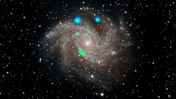 This visible-light image of NGC 6946 comes from the Digital Sky Survey, and is overlaid with data from NASA's NuSTAR observatory (in blue and green). ULX-4 is the green blob near the bottom of the galaxy. Image credit: NASA / JPL-Caltech.