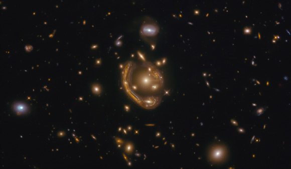 This Hubble image shows GAL-CLUS-022058-38303, the largest, nearly-complete Einstein ring known. The image is made up of observations from Hubble's Wide Field Camera 3 (WFC3) in the infrared and optical parts of the spectrum. Three filters were used to sample various wavelengths. The color results from assigning different hues to each monochromatic image associated with an individual filter. Image credit: NASA / ESA / Hubble / Saurabh Jha, Rutgers the State University of New Jersey / L. Shatz.