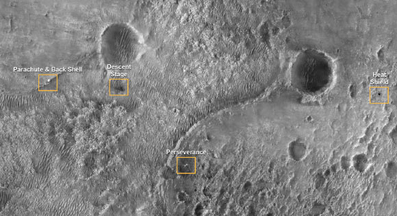 This first image of NASA's Perseverance Rover on the surface of Mars from the High Resolution Imaging Experiment (HiRISE) camera aboard NASA's Mars Reconnaissance Orbiter shows the many parts of the Mars 2020 mission landing system that got the rover safely on the ground. The image was taken on February 19, 2021. The image points out the locations of the parachute and back shell, the descent stage, the Perseverance rover, and the heat shield. Each inset shows an area about 200 m (650 feet) across. The rover itself sits at the center of a blast pattern created by the hovering descent stage that lowered it there using the sky crane maneuver. The descent stage flew off to crash at a safe distance, creating a V-shaped debris pattern that points back toward the rover. Earlier in the landing sequence, Perseverance jettisoned its heat shield and parachute, which can be seen on the surface in the separate locations illustrated. These objects are highly visible on the surface of Mars now but will become dustier with time and slowly fade into the background over years. HiRISE will continue to image the Perseverance landing site to track the progress of the rover and changes with the other pieces of hardware that accompanied it. Image credit: NASA / JPL-Caltech / University of Arizona.