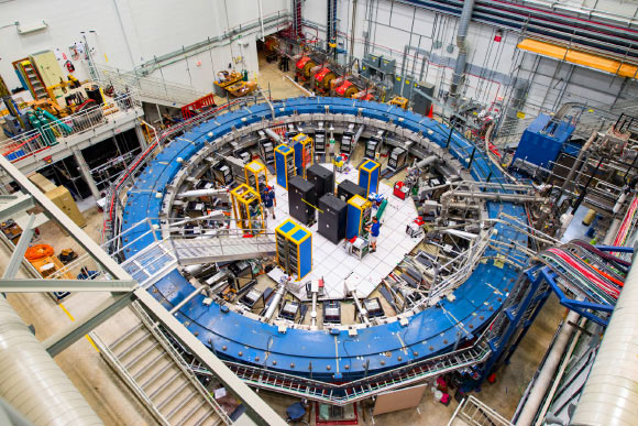 The Muon g-2 ring sits in its detector hall amidst electronics racks, the muon beamline, and other equipment. Image credit: Reidar Hahn.